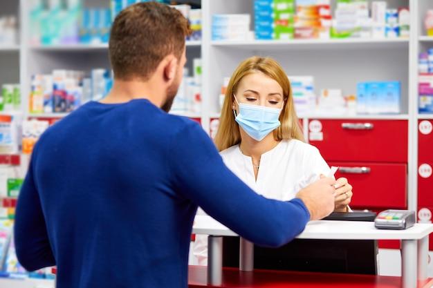 Profesjonalny farmaceuta kobieta pomaga klientowi płci męskiej