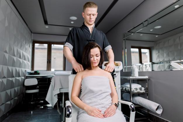 Profesjonalny fizjoterapeuta robi masaż manualny młodej kobiecie ramiona i plecy w gabinecie rehabilitacji