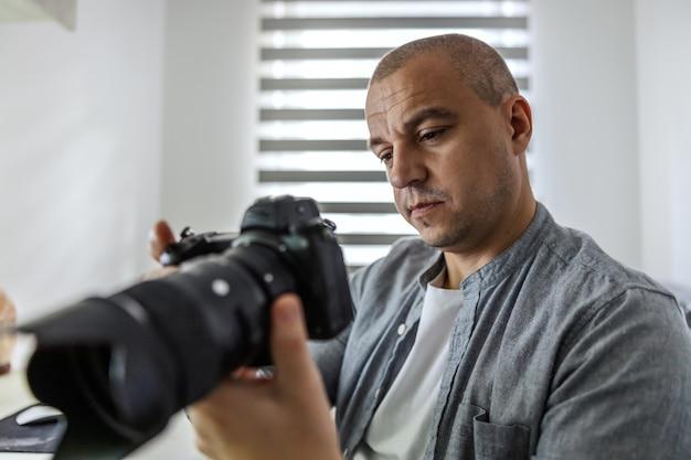 Profesjonalny fotograf człowiek oglądający zdjęcia, które właśnie zrobił profesjonalnym aparatem