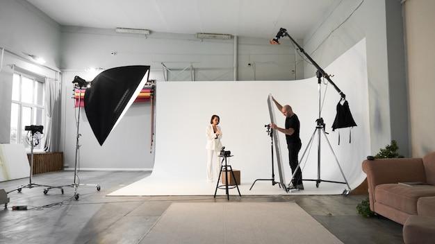 Profesjonalny fotograf mężczyzna robi zdjęcia pięknej modelki na aparat w studio