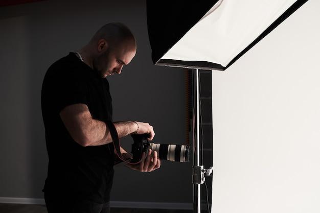Profesjonalny fotograf mężczyzna robi zdjęcia w studio