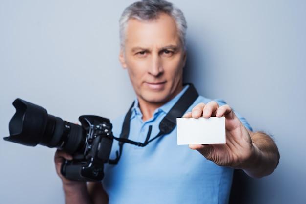 Profesjonalny fotograf. portret pewnego siebie dojrzałego mężczyzny w koszulce trzymającego aparat i wyciągającego wizytówkę, stojąc na szarym tle