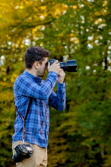 Profesjonalny fotograf w akcji z dwoma aparatami na ramiączkach