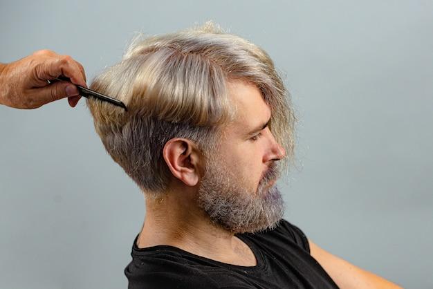 Profesjonalny fryzjer dokonuje strzyżenia włosów. koncepcja fryzjera. męski klient dostaje strzyżenie przez fryzjera. zamknij się portret.