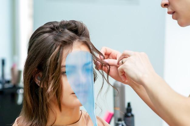 Profesjonalny fryzjer dokonywanie fryzury dla kobiety, podczas gdy maska ochronna na jej twarzy w salonie kosmetycznym.