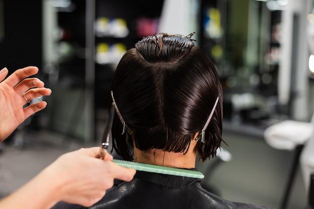 Profesjonalny fryzjer dziewczyna wykonuje fryzurę klienta. dziewczyna siedzi w masce w salonie piękności