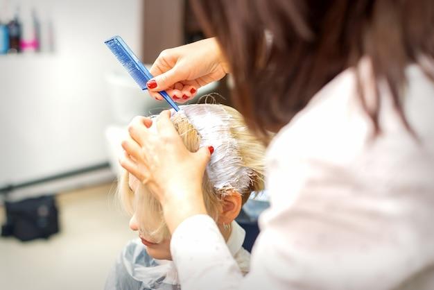Profesjonalny fryzjer, farbowanie włosów swojej klientki na biały kolor w salonie fryzjerskim