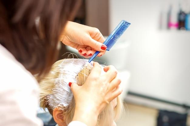 Profesjonalny fryzjer farbujący włosy klientki