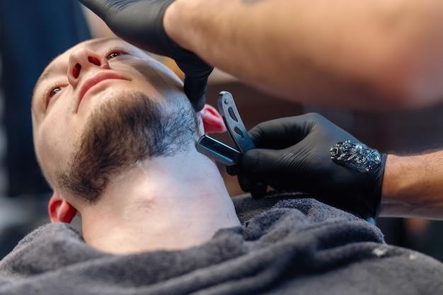 Profesjonalny fryzjer goli brodę klienta prostą brzytwą. strzyżenie brody staromodnym ostrzem u fryzjera. przystojny mężczyzna macho coraz brodę ogolone w studio. strzał z bliska.
