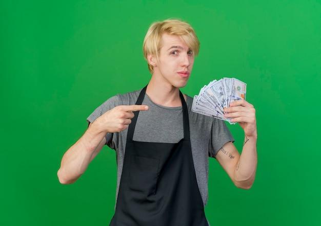 Profesjonalny fryzjer mężczyzna w fartuch trzymając gotówkę, wskazując palcem wskazującym na pieniądze, patrząc pewnie