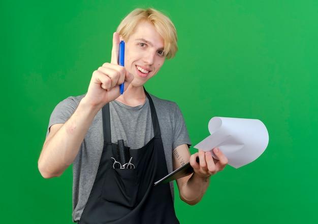 Profesjonalny fryzjer mężczyzna w fartuch trzymając schowek z pustymi stronami i uśmiechem pióra