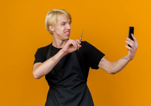 Profesjonalny fryzjer mężczyzna w fartuch trzymając smartfon po rozmowie wideo pokazując nożyczki z przodu uśmiechnięty stojący nad pomarańczową ścianą