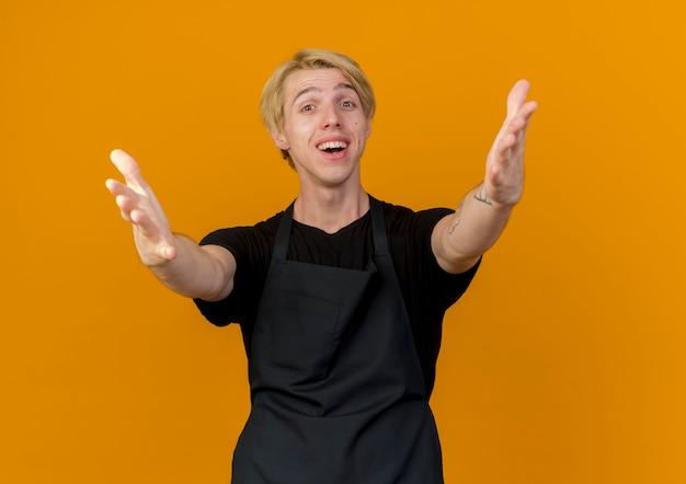 Profesjonalny fryzjer mężczyzna w fartuchu patrząc z przodu robi powitalny gest otwierając szeroko ręce uśmiechając się stojąc nad pomarańczową ścianą