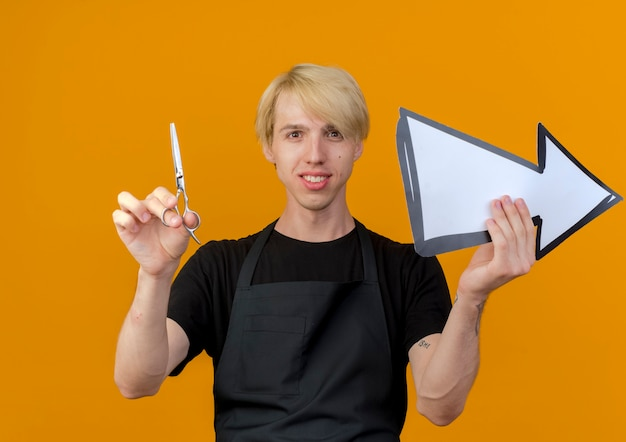 Profesjonalny fryzjer mężczyzna w fartuchu trzyma białą strzałkę i nożyczki patrząc na przód uśmiechnięty pewny siebie stojący nad pomarańczową ścianą