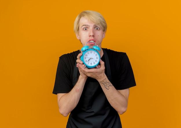 Profesjonalny fryzjer mężczyzna w fartuchu trzymając budzik patrząc z przodu zmartwiony stojąc nad pomarańczową ścianą