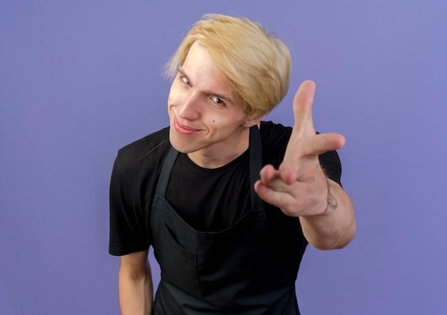 Profesjonalny fryzjer mężczyzna w fartuchu, wskazując ramieniem na ciebie, uśmiechając się, stojąc na niebieskiej ścianie