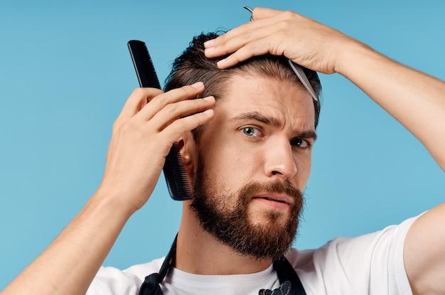 Profesjonalny fryzjer mężczyzna w szarym fartuchu robi jego włosy