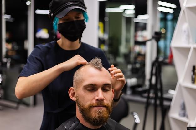 Profesjonalny fryzjer noszący ochronną maskę na twarz, robi fryzurę dla europejskiego brodatego brutalnego mężczyzny w salonie kosmetycznym