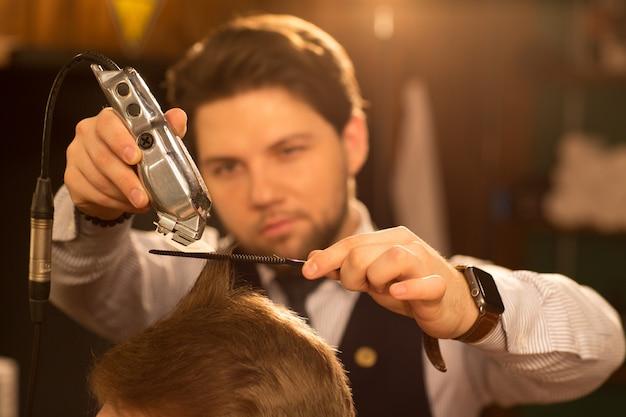 Profesjonalny fryzjer pracujący w swoim zakładzie fryzjerskim