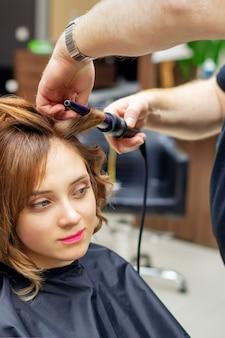 Profesjonalny fryzjer skręca loki długich jasnobrązowych włosów kobiety z lokówką w salonie kosmetycznym. procedury fryzjerskie