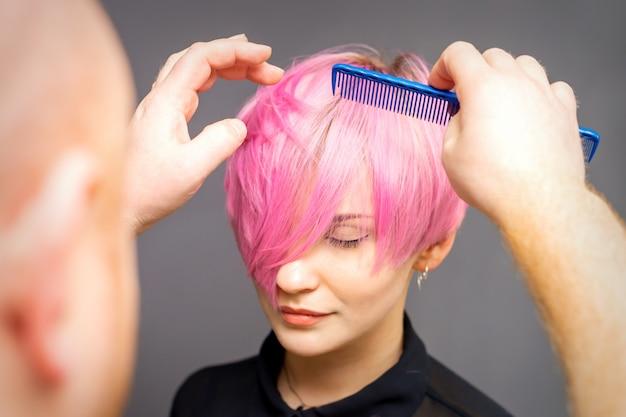 Profesjonalny fryzjer sprawdza fryzurę grzebieniem młodej pięknej kaukaskiej kobiety