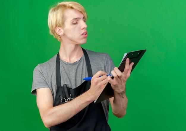 Profesjonalny fryzjer w fartuch, trzymając schowek i długopis, pisząc coś z poważną miną