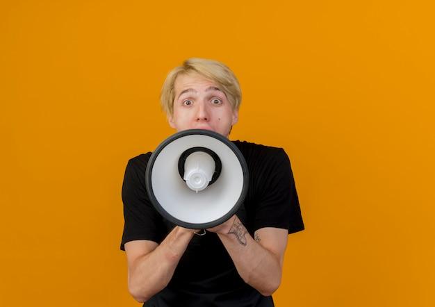 Profesjonalny fryzjer w fartuchu krzyczy do megafonu głośno stojącego nad pomarańczową ścianą