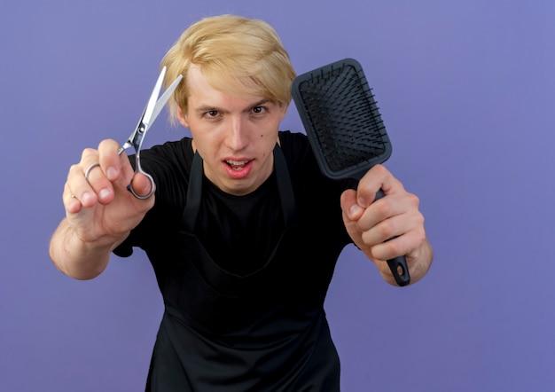 Profesjonalny fryzjer w fartuchu pokazano nożyczki i szczotkę do włosów, patrząc z przodu z poważną twarzą stojącą nad niebieską ścianą