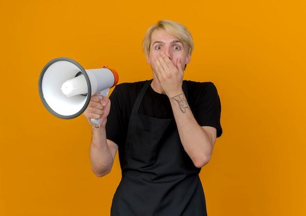 Profesjonalny fryzjer w fartuchu trzymając megafon zakrywający usta ręką będąc w szoku stojąc nad pomarańczową ścianą