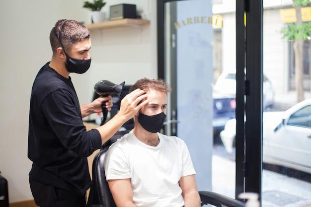 Profesjonalny fryzjer w masce ochronnej obcinającej włosy klientowi podczas koronawirusa