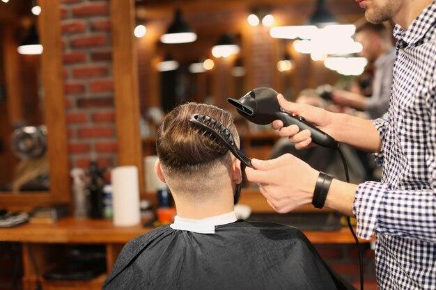 Profesjonalny fryzjer współpracujący z klientem w salonie fryzjerskim