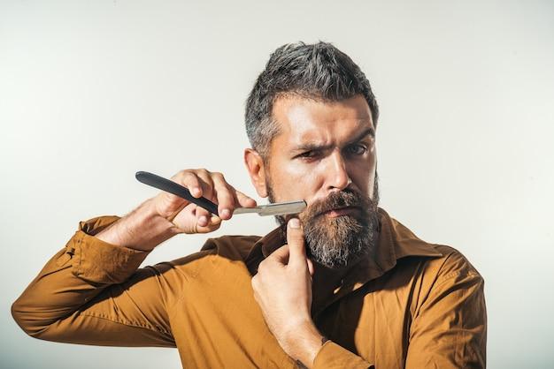Profesjonalny fryzjer z gęstą brodą i wąsami, trzymający brzytwę. fryzjer demonstruje ostre ostrze akcesoriów fryzjerskich. młody brodaty macho do golenia żyletką.