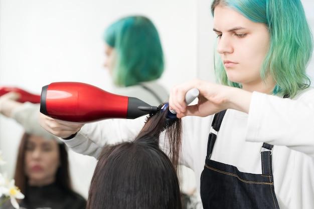 Profesjonalny fryzjer z zielonymi włosami suszy klientce włosy czerwoną suszarką i niebieskim grzebieniem