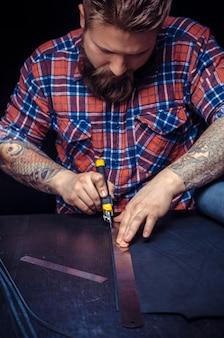 Profesjonalny garbarz tworzy nową galanterię skórzaną w swoim warsztacie