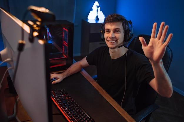 Profesjonalny gracz cybernetyczny prowadzący transmisje na żywo, machający ręką do obserwujących i subskrybentów swojego kanału internetowego