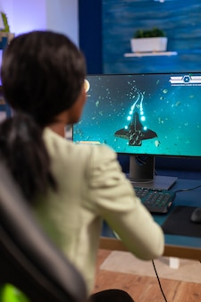 Profesjonalny gracz e-sportowy podczas mistrzostw online z joystickiem. konkurencyjna kobieta gracza cybernetycznego podczas turnieju gier wideo używa profesjonalnego joysticka.