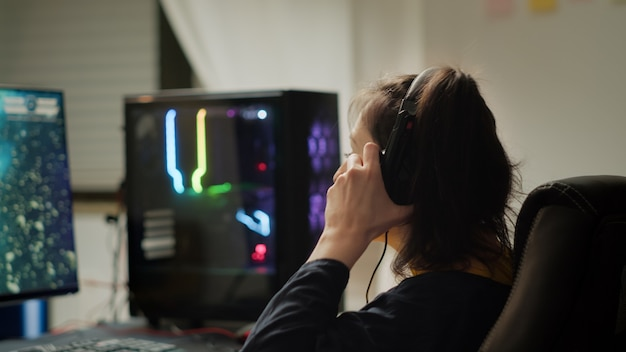 Profesjonalny gracz esport z zestawem słuchawkowym, grający w konkurencyjne gry wideo na turnieju gier cybernetycznych. wirtualne mistrzostwa w cyberprzestrzeni, e-sportowiec grający na potężnym komputerze osobistym rgb