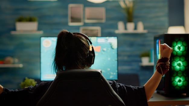 Profesjonalny gracz grający w gry wideo z nową grafiką wygrywający mistrzostwa, siedzący w pokoju gier. wirtualna kosmiczna strzelanka w cyberprzestrzeni, e-sportowiec wykonujący turniej na profesjonalnym komputerze rgb