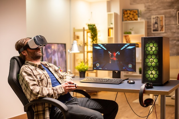 Profesjonalny gracz korzystający z zestawu vr do grania na potężnym komputerze późno w nocy w swoim salonie