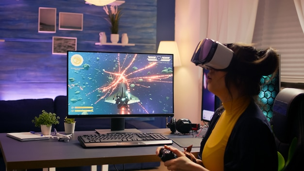 Profesjonalny gracz noszący gogle vr siedzący na fotelu do gier, grający w kosmiczną strzelankę online
