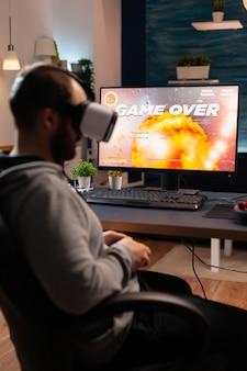 Profesjonalny gracz noszący gogle vr siedzący na fotelu do gier, grający w strzelankę online. pokonany mężczyzna przegrywający turniej gier wideo za pomocą joysticka późno w nocy w salonie.