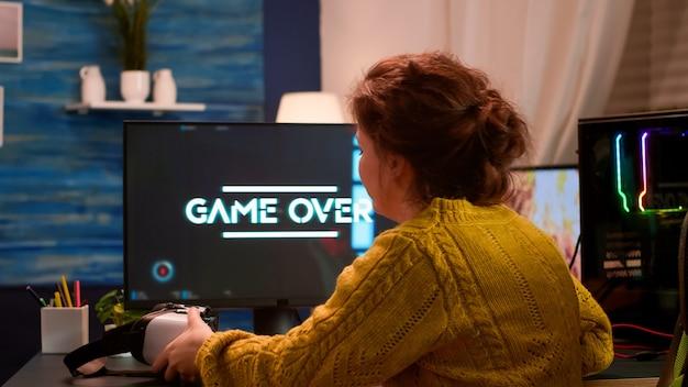 Profesjonalny gracz noszący zestaw słuchawkowy do rzeczywistości wirtualnej, trzymający bezprzewodowy kontroler wykonujący strzelankę