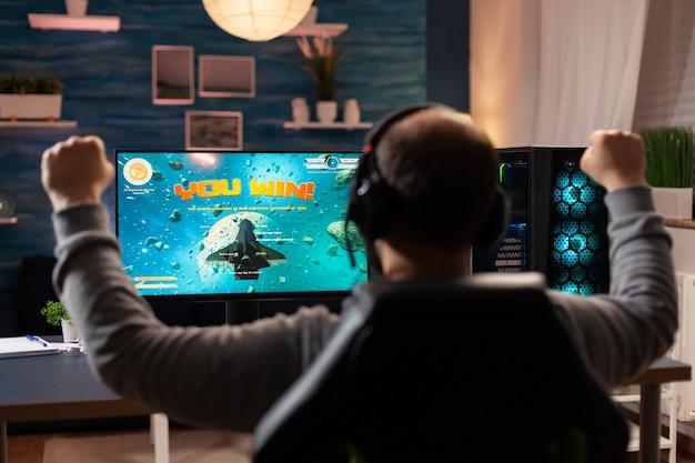 Profesjonalny gracz podnoszący ręce z powodu wygrania turnieju w słuchawkach. cyber przesyłania strumieniowego online podczas turnieju w grach przy użyciu technologii sieci bezprzewodowej