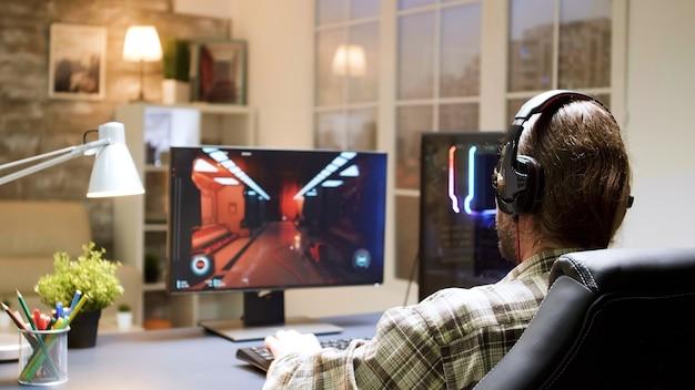 Profesjonalny gracz z długimi włosami zakłada słuchawki z mikrofonem i zaczyna grać w strzelankę na komputerze osobistym.