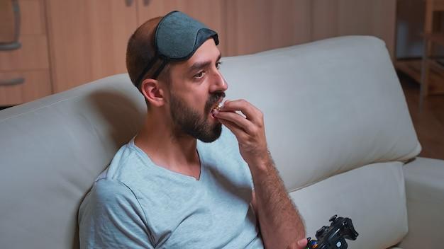 Profesjonalny gracz z maską do spania siedzący przed telewizorem, grający w gry wideo