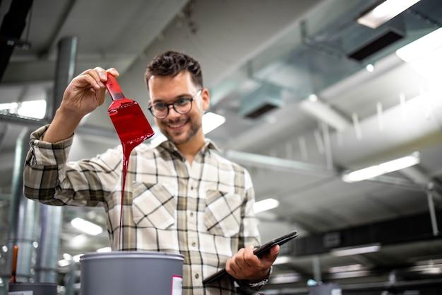Profesjonalny grafik lub inżynier sprawdzający wartości kolorów na nowoczesnej maszynie drukarskiej