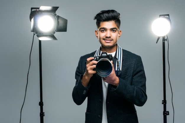 Profesjonalny indyjski młody fotograf robi zdjęcia w studio z lekkim
