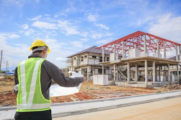 Profesjonalny inżynier architekt pracownik z hełmem ochronnym i papierem plany na budowie