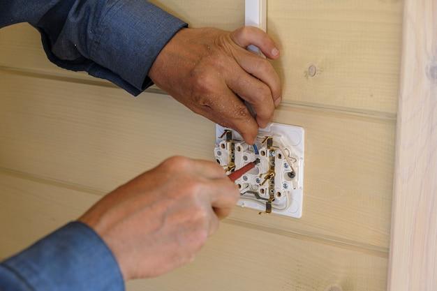 Profesjonalny inżynier elektryk wykonuje montaż gniazd elektrycznych i okablowania w nowym drewnianym domu