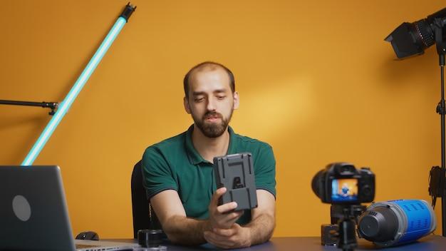 Profesjonalny kamerzysta pokazujący baterię v mount do kamery podczas nagrywania odcinka vloga. nowoczesna technologia typu v-lock, dystrybucja online z gwiazdą mediów społecznościowych